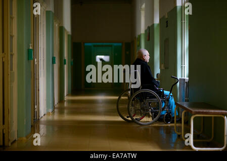 Old man on a wheelchair looking out of a window alone on a long corridor - Stock Photo