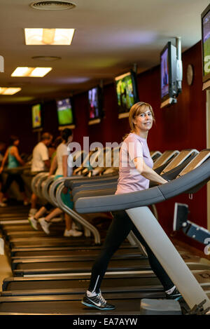 Mature woman walking on treadmill at the gym - Stock Photo