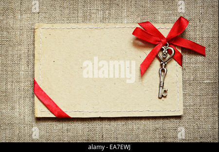 Greeting card with red ribbon and a key on canvas background - Stock Photo