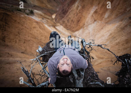 Man sitting on the edge of a high cliff, adrenaline, courage and risk concept - Stock Photo