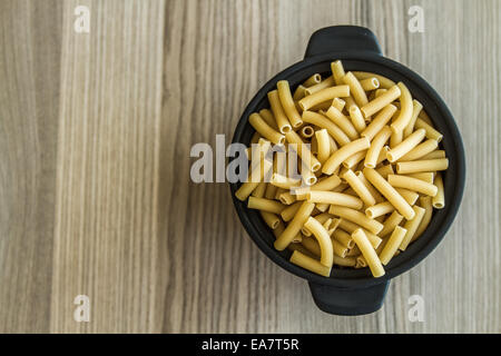 Italian dry pasta in a black Bow on a wooden table - Stock Photo