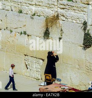 Jew praying and young boy at Western wall Jerusalem Israel - Stock Photo