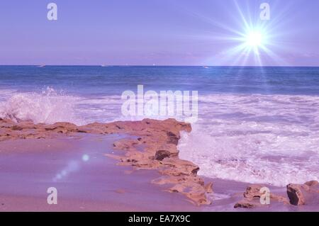 Star burst over rocky beach - Stock Photo