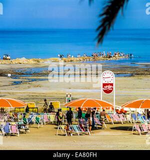 People bathing with black mud at Ein Gedi spa beach at Dead Sea Israel - Stock Photo