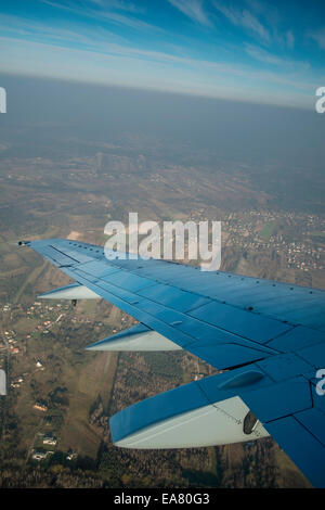 View from window seat, Airplane flying above clouds - Stock Photo