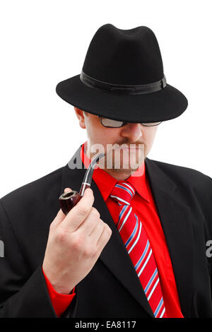 Confident man in black with pipe, wearing hat and dark glasses - Stock Photo