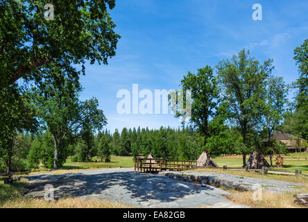 The grinding rock with Miwok bark homes behind, Indian Grinding Rock State Historic Park, Southern Gold Country, - Stock Photo