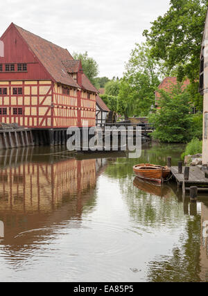 Half Timbered river houses of old Aarhus. Two small row boats float in the water in front of  traditional Danish - Stock Photo
