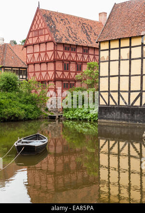 Half Timbered houses of old Aarhus. A small row boat is anchored in the calm water in front of traditional Danish - Stock Photo