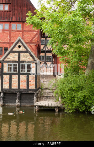 Aarhus Old Town Dock. Half Timbered and bricked houses of old Aarhus cluster around a wooden dock.  Ducks float - Stock Photo