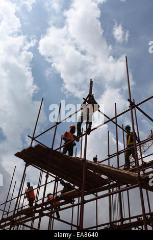 Workers on a scaffolding at a construction site in Lagos Nigeria - Stock Photo
