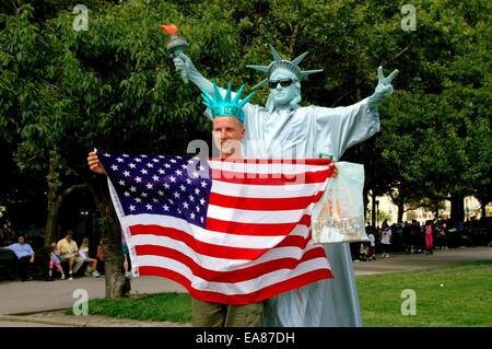 NYC:  European visitor holding an American flag poses with one of the ubiquitous Lady Liberty mimes in Battery Park - Stock Photo