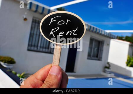 a man hand holding a signboard with the text for rent written in it in front of a house - Stock Photo