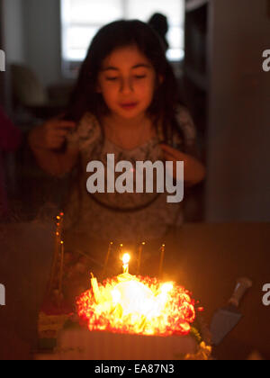 Young girl at home blowing out candles on a Birthday Cake. - Stock Photo