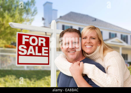Affectionate Happy Couple in Front of New House and For Sale Real Estate Sign. - Stock Photo