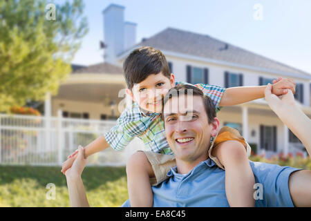 Mixed Race Father and Son Playing Piggyback in Front of Their House. - Stock Photo