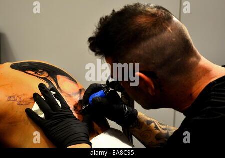 Tattoo artist tattooing portrait on back of woman - Stock Photo