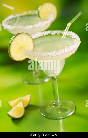 Two tequila margaritas with tequila, lime, and salt against a vibrant abstract green background. - Stock Photo