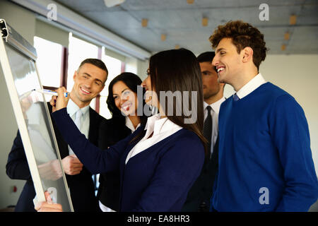 Happy business team with flip board in office - Stock Photo