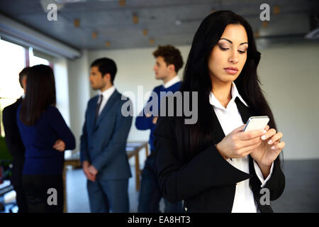 Beautiful woman using smartphone with colleagues on background - Stock Photo
