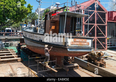 Dockyard workers reapairing a fishing cutter in a dry dock at V&A Waterfront, Cape Town, South Africa - Stock Photo