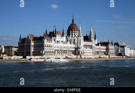 Landscape view of Hungarian Parliament building with blue sky, Danube in foreground and cruise boat sailing in front - Stock Photo