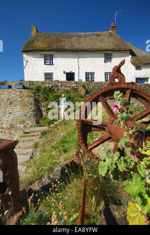 Rusting metal wheel with white painted thatched cottage in background & lady walking down steps to Cadgwith Harbour - Stock Photo