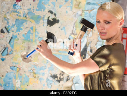Berlin, Germany. 8th Nov, 2014. Model Franziska Knuppe chisels away on a piece of the Berlin Wall during the Bild - Stock Photo