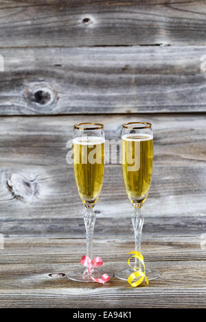 Vertical image of Golden champagne in elegant glasses on rustic wood with ribbons - Stock Photo