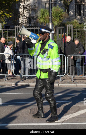 London Community Support Officer takes crowd control measures to ease congestion around Tower Hill Underground Station. - Stock Photo
