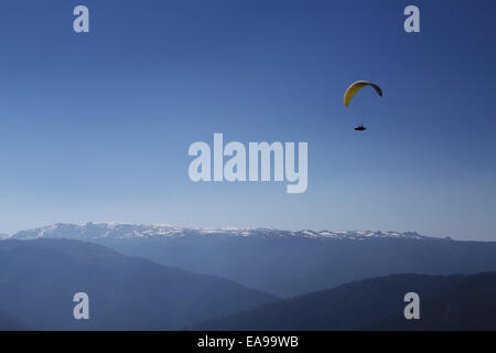 A paraglider gliding near the takeoff of Azinha, in Manteigas, Portugal, with the snow capped Serra da Estrela in - Stock Photo