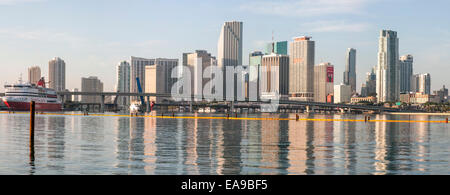 High-rises of the Miami skyline are reflected in the calm waters of Biscayne Bay in the early morning sunlight, - Stock Photo