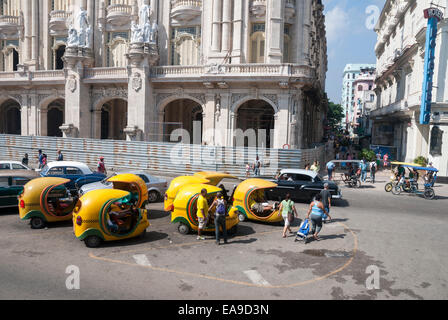 Distinctive Coco taxis wait for tourist business while parked on Paseo del Prado in central Havana Cuba - Stock Photo