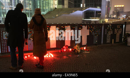 Berlin, Germany. 09th Nov, 2014. People look at candles and flowers set out before memorial crosses for those who - Stock Photo
