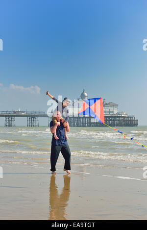 Grandfather with grandson flying a kite on the beach at Eastbourne. East Sussex. UK - Stock Photo