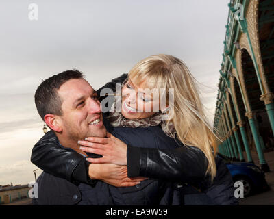 A couple enjoying a day out at the British seaside in Brighton in warm winter clothing - Stock Photo