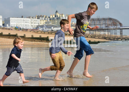 A group of boys running into the sea at Eastbourne. East Sussex. UK - Stock Photo