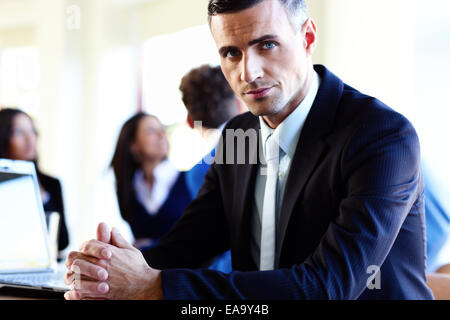 Serious businessman sitting at the table in front of colleagues - Stock Photo