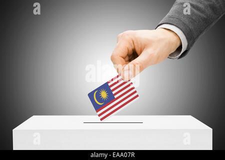 Voting concept - Male inserting flag into ballot box - Malaysia - Stock Photo