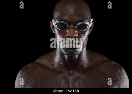 Portrait of confident male swimmer looking at camera against black background. Close-up image of muscular young - Stock Photo