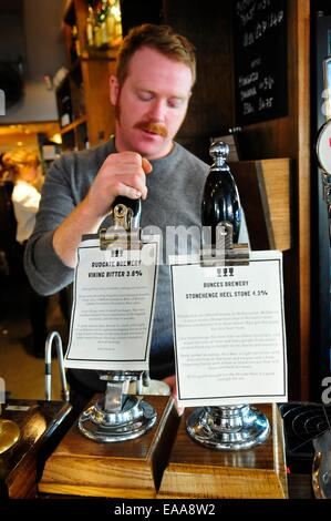 Barman pulling a pint of beer at The Draft House pub in Battersea, London - Stock Photo