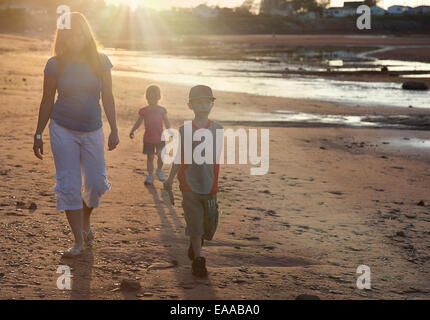 mother and children walking on beach in sunset - Stock Photo
