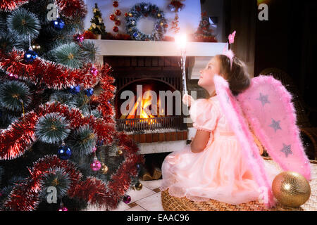little fairy girl with magic wand near a Christmas tree, fireplace on background - Stock Photo