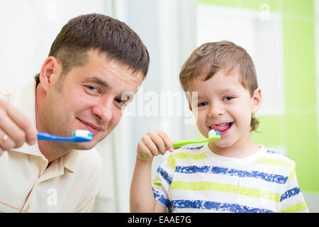 father and kid son brushing teeth in bathroom - Stock Photo