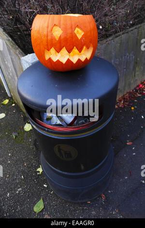A pumpkin discarded after Halloween on top of a street litter bin. - Stock Photo