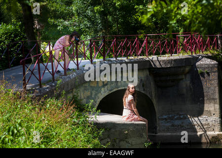 A teenage girl photographs another girl sitting on an old river bridge at Jarnac - Stock Photo