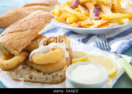 deep fried calamari on bread with sauce and fries - Stock Photo