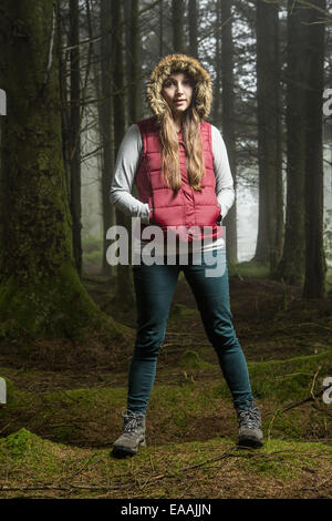 A young woman standing in a forest with her hood up and hands in her pockets. - Stock Photo