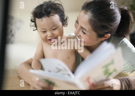 Mother reading to her baby boy. - Stock Photo