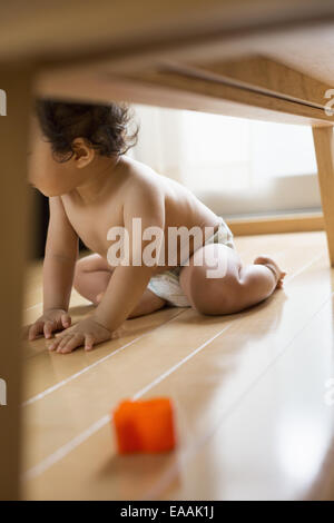 Baby boy sitting under table. - Stock Photo